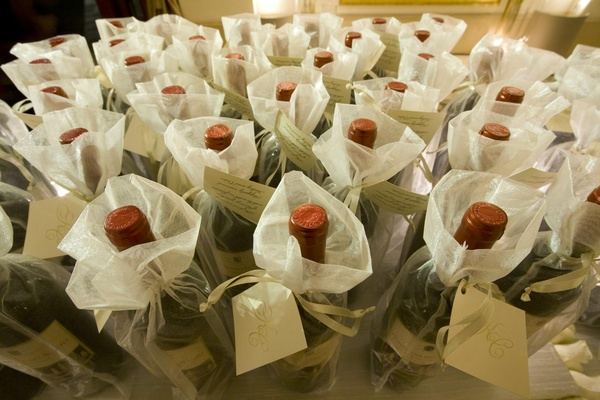 Wedding favors of wine bottles in sheer white bags