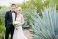 bride and groom stand in arizona desert with white bouquet