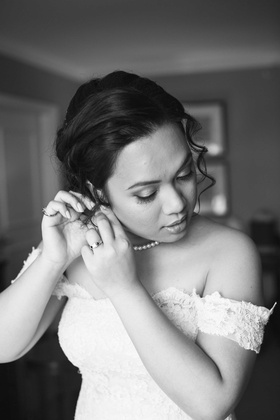 black and white photo of bride getting ready putting earrings in off the shoulder wedding dress