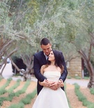 bride in monique lhuillier crop top wedding dress held by groom in armani standing under trees