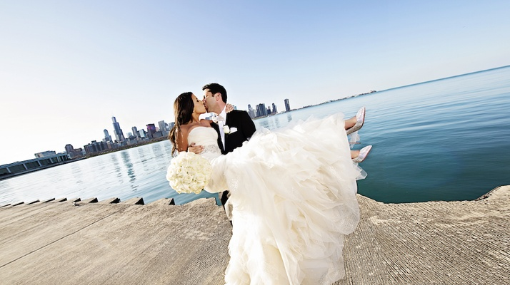 Bride in Vera Wang wedding dress kisses groom at Chicago Lakefront Trail