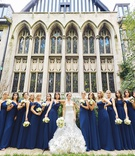 bride in strapless mermaid wedding dress ruffle skirt bridesmaids in navy blue mismatch neckline
