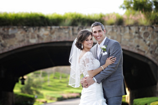 Woman in lace wedding dress and man in grey suit