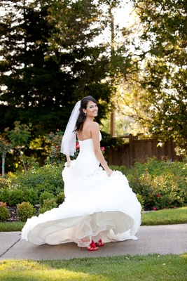 Bride wearing Maggie Sottero wedding dress and hot pink shoes