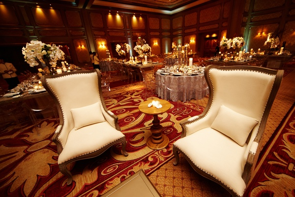 White tall-back arm chairs at indoor ballroom reception