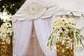 outside of white wedding reception tent with embellished gold monogram