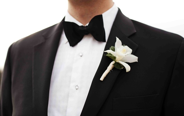Groomsman in tuxedo and bow tie with white boutonniere