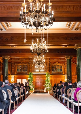wedding ceremony wood paneling chandeliers greenery arch white aisle runner wood round back chairs
