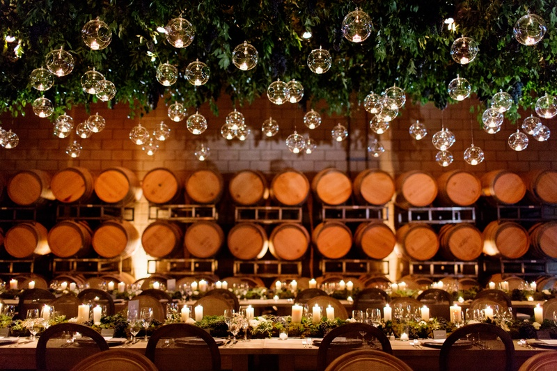 Wine barrel room wedding venue with glass orb candlelight
