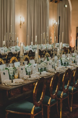 wedding reception long table with gold green chairs tall taper candles white greenery flowers luxury