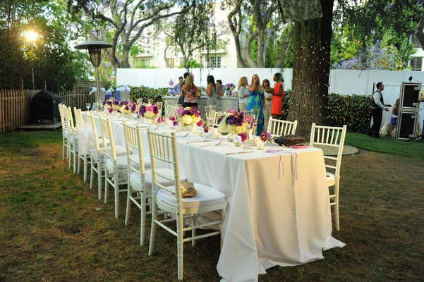 long white table with purple and pink centerpieces