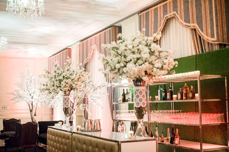 Tufted bar with glasses and bottles on shelf in front of hedge wall greenery lace around glass vases