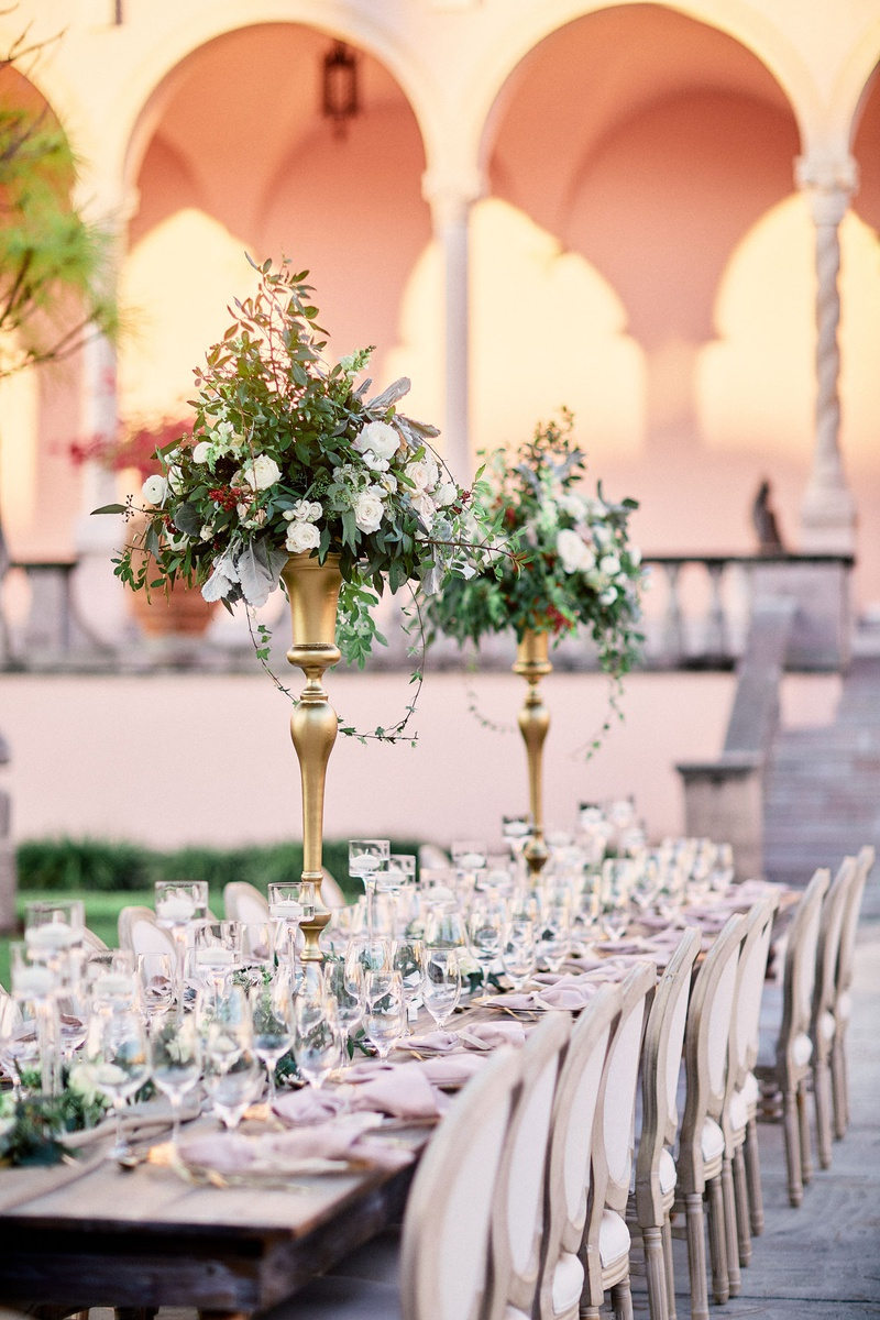 ringling museum outdoor wedding reception, long tables with gold stands with greenery centerpieces
