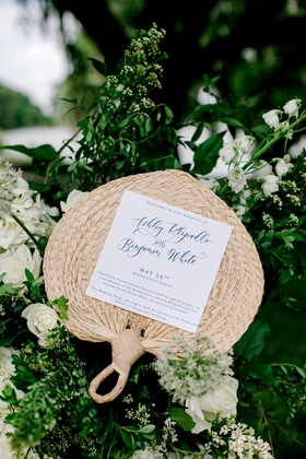 wedding ceremony program on woven wicker rattan fan navy blue lettering white flowers greenery