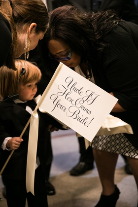 """ring bearer with """"here comes the bride"""" sign for his uncle's wedding"""