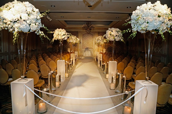 Wedding ceremony with tall arrangements of white hydrangeas, roses, orchids, candles, gold chairs