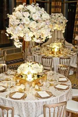 white table linens with details gold charger plates mirrored stands glass vases white rose flowers
