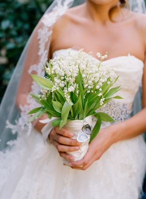 Bride holds bouquet of lilies of the valley with locket