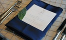 Wedding reception table with navy napkin and leaf