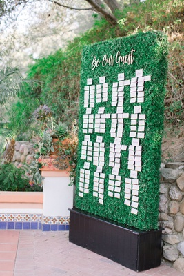 wedding reception tall green hedge wall with escort cards be our guest calligraphy sign outdoor