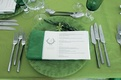Wedding reception place setting with green tablecloth, napkin, and glasses