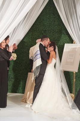 Washington DC wedding ceremony tall green hedge wall white drapery chuppah white tile kiss jewish