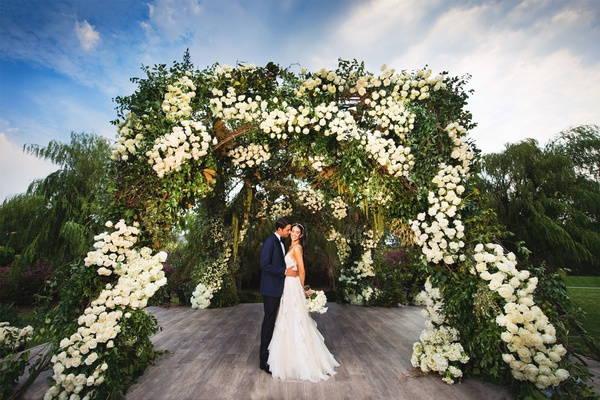jewish wedding portrait bride groom wood aisle under greenery white flower arch chuppah outdoor