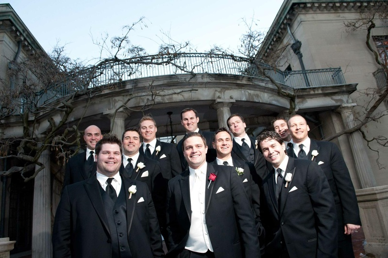 Groom in black tuxedo, white vest, red rose boutonniere with groomsmen in black tuxedos