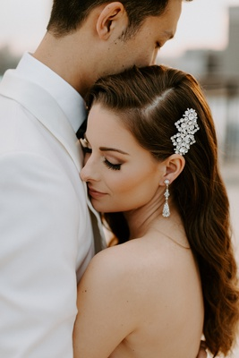bride portrait with groom white jacket pretty makeup side part long hair headpiece earrings