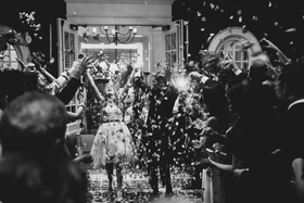 black and white photo of grand exit with flower petals thrown over newlyweds
