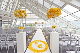 Wedding ceremony at the Adler Planetarium with bride and groom's monogram in yellow rose petals