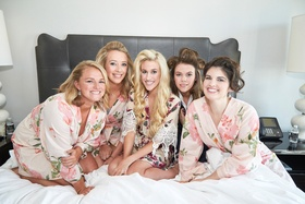 bridesmaids and bride on bed in bridal suite wearing pink floral robes