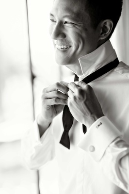black and white photo of groom donning tie tying smiling posing california wedding ceremony classic