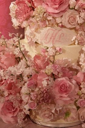 wedding cake covered in pink sugar flowers