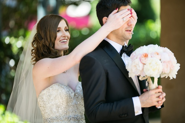 bride covers groom's eyes right before the first look, groom