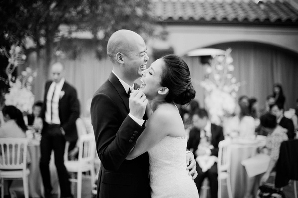 black and white photo of bride and groom laughing during first dance