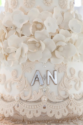 Silver wedding initials on cake with sugar flowers and lace