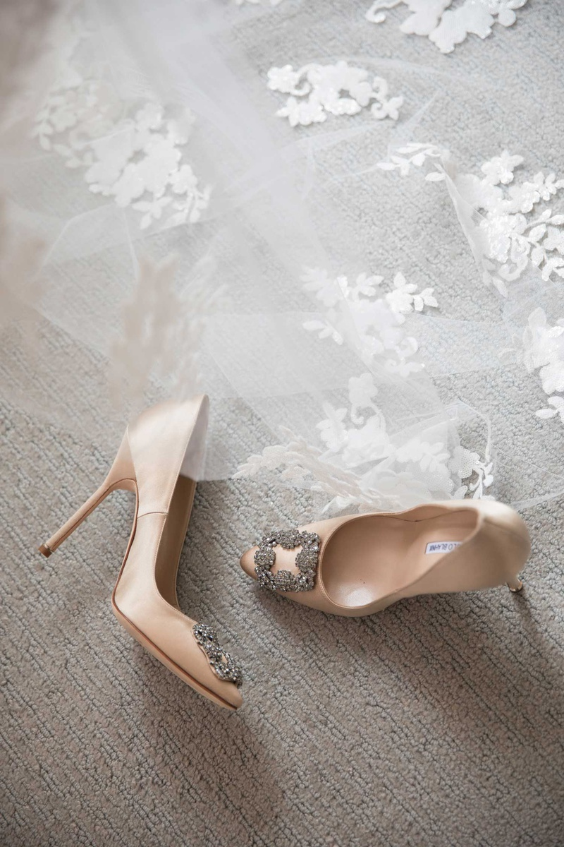 Manolo Blahnik nude wedding heels with crystal buckle detail at toe pumps ceil with flowers