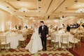 bride and groom looking at wedding ballroom decor white and gold color palette neutral centerpieces