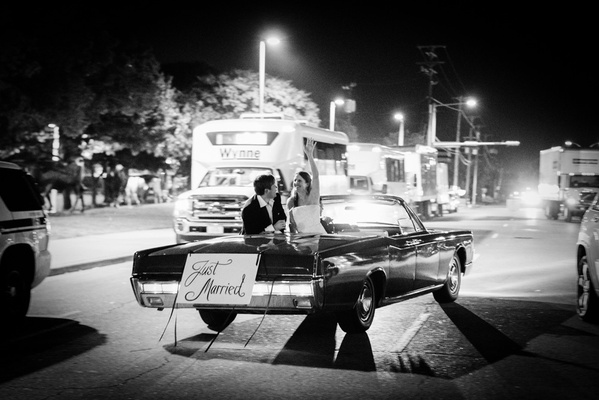 black and white photo of bride and groom newlyweds in vintage convertible getaway car