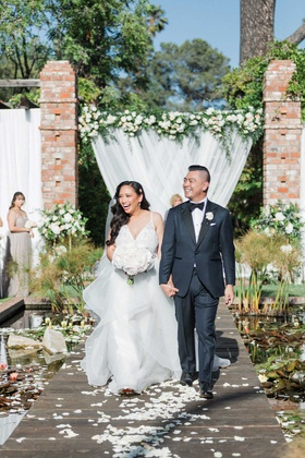 bride in v neck hayley paige wedding dress groom tuxedo belmond el encanto wood aisle lily pads pond