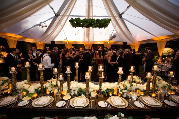 wedding reception guests on dance floor wood table greenery chandelier orbs