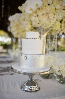 Three layer cake with silver bottom tier and white top layers