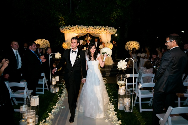 Bride and groom recessional at outdoor evening wedding