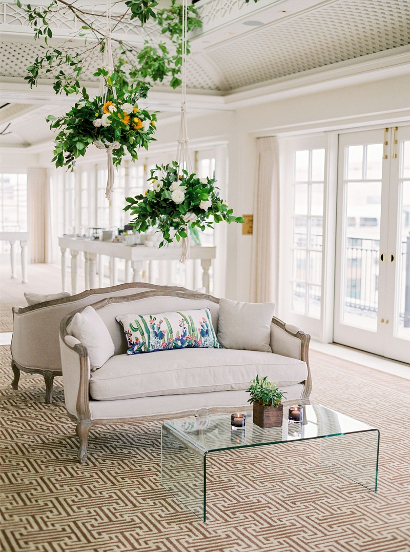 Wedding reception hanging flower arrangements from ceiling antique settee with watercolor pillow