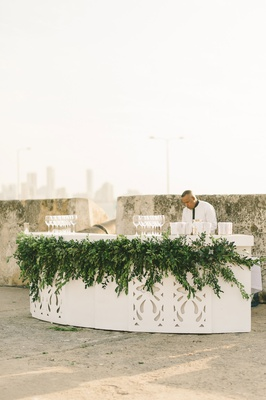 outdoor bar for champagne and wine at ceremony laser cut cutouts greenery bartender skyline