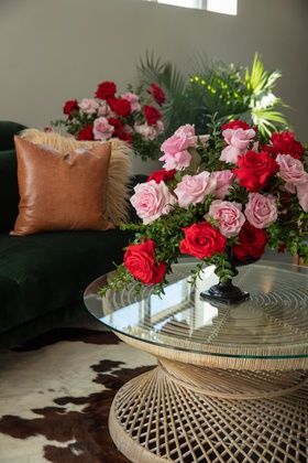 small arrangement of pink roses and red roses on glass top wicker woven tables