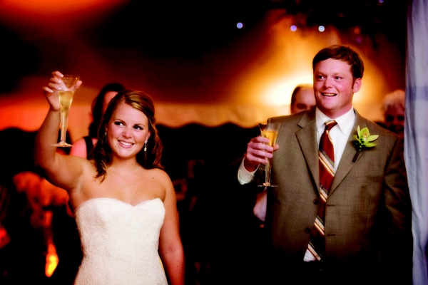 Bride in Vera Wang gown and groom in a tan suit and striped tie
