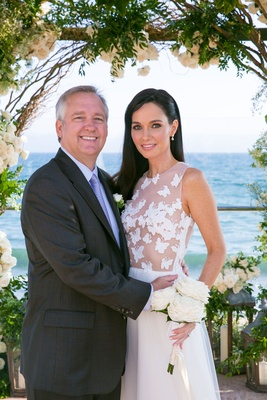 Shannon Miller Turner and Jon Turner at vow renewal butterfly wedding dress and white bouquet ocean