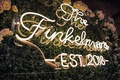 wedding reception custom neon sign on hedge wall with wedding year and last name
